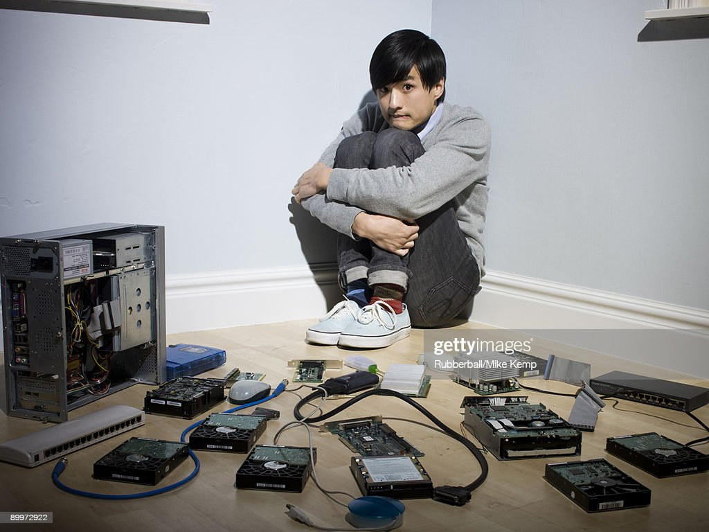 man in the corner surrounded by computer parts