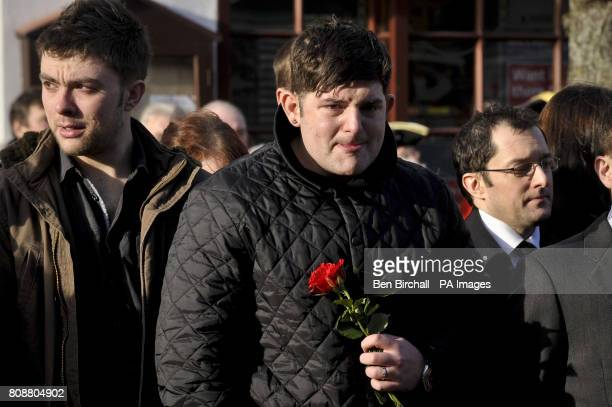 A man in the crowd on Wootton Bassett High Street holds a single red rose and peeks out to watch as the hearse carrying the coffin of Private Martin...