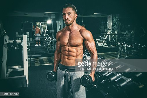 Man in the gym exercising with dumbbells : Stockfoto
