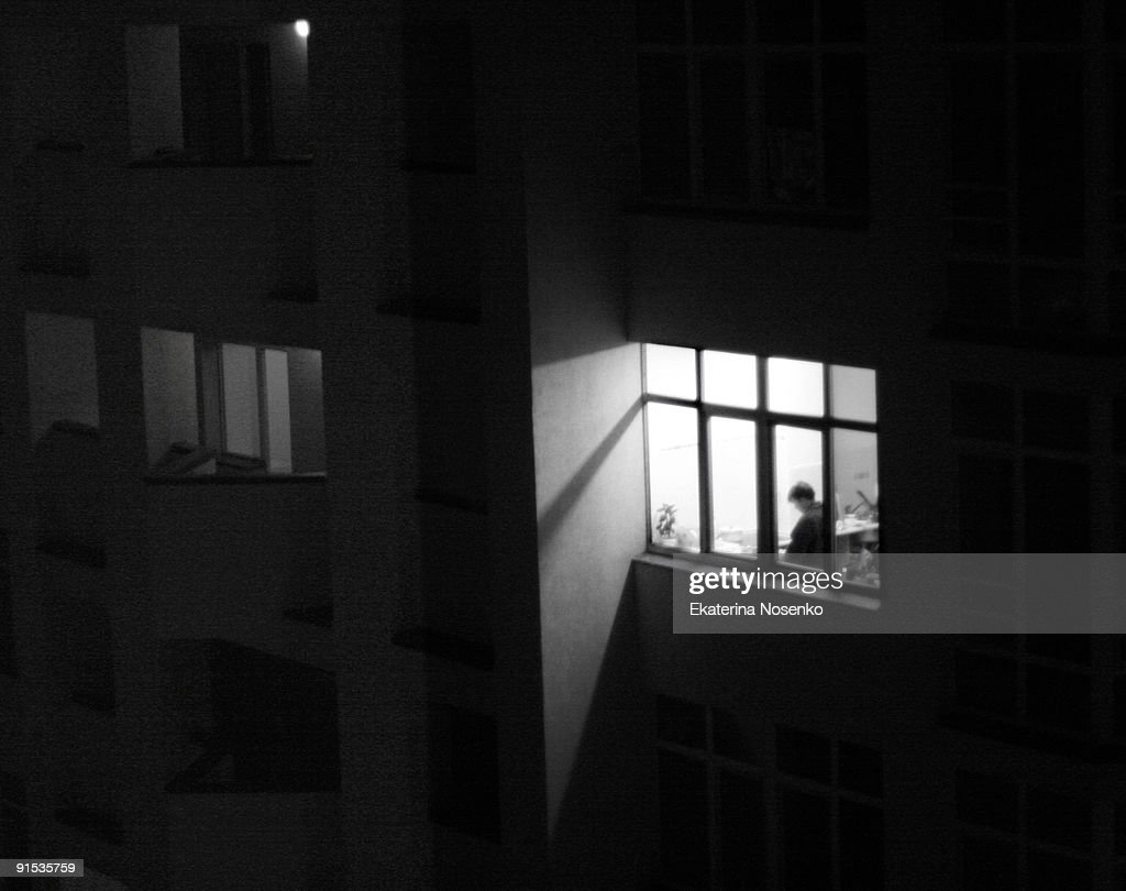 A man in the lit up window