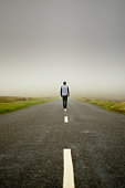 Man stands in the middle of an empty road in Dartmoor, England