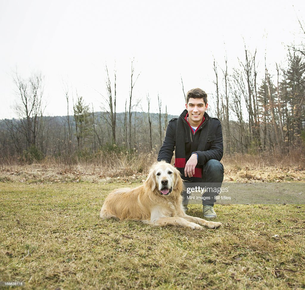 A man in the open air, on a winter day.  Stroking a golden retriever dog.  : Stock Photo