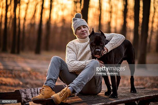 Man in the park hugging Cane Corso