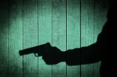Man in the Shadows with handgun, on natural wooden background, with space for text or image.