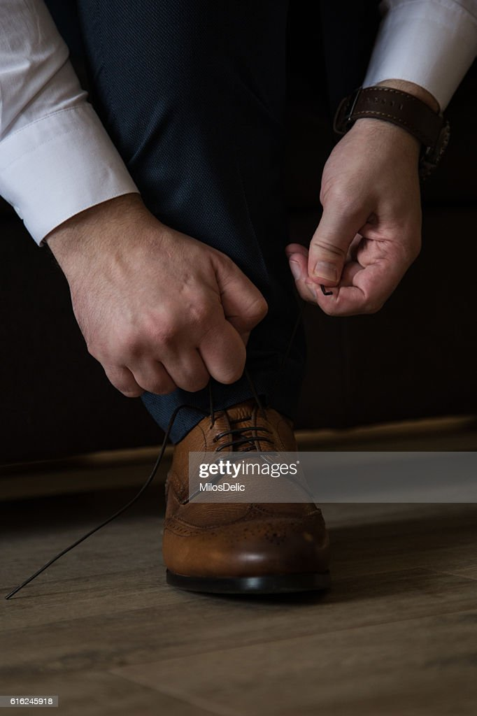 Man in the suit tying his shoelaces : Stock-Foto