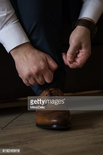 Man in the suit tying his shoelaces : Foto stock