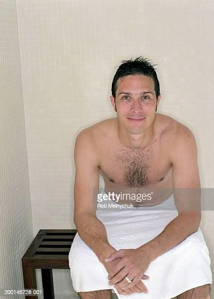 Man in towel sitting in steam room, portrait