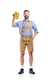 Handsome hipster young man in traditional bavarian clothes holding a mug of beer. Oktoberfest. Studio shot on white background, isolated.