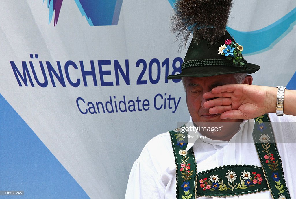 A man in traditional clothes sits in front of a Munich 2018 sign during the Public Viewing for the International Olympic Committee Decision at Mohrenplatz on July 6, 2011 in Garmisch-Partenkirchen, Germany. Today the IOC who meets in Durban decide if Munich, Annecy or PyoengChang will get the Olympic Winter Games 2018.