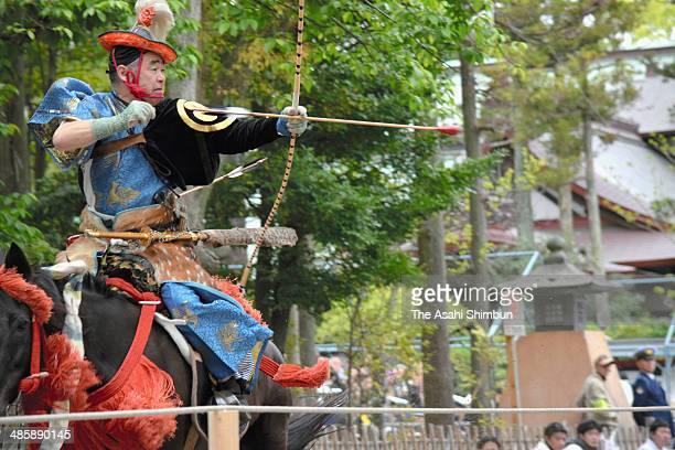 A man in traditional costume aims at a target at Tsurugaoka Hachimangu Shrine on April 20 2014 in Kamakura Kanagawa Japan