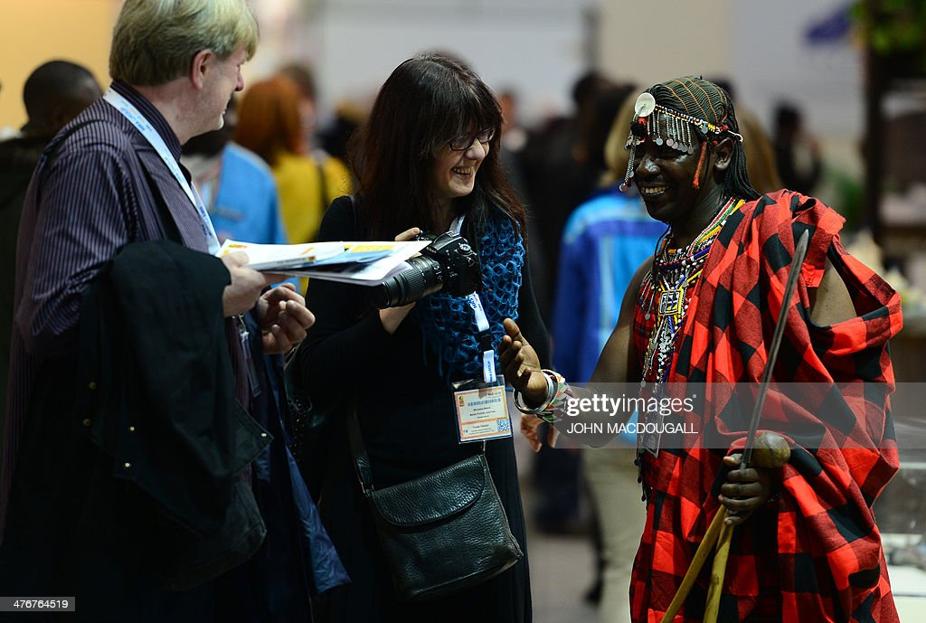 A man in traditional garb interacts with fair-goers at the Kenya stand of the ITB International Travel Trade Fair in Berlin March 5, 2014. The ITB opens from March 5 to 9, 2014. AFP PHOTO / JOHN MACDOUGALL