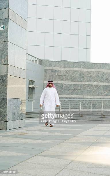 Man in traditional Middle Eastern attire walking towards camera, Dubai, UAE
