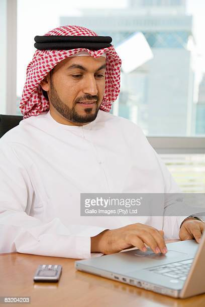 Man in traditional Middle Eastern attire working on laptop, Dubai cityscape in background, UAE