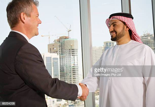 Man in traditional Middle Eastern dress shaking hands with Western businessman, Dubai cityscape in background, UAE