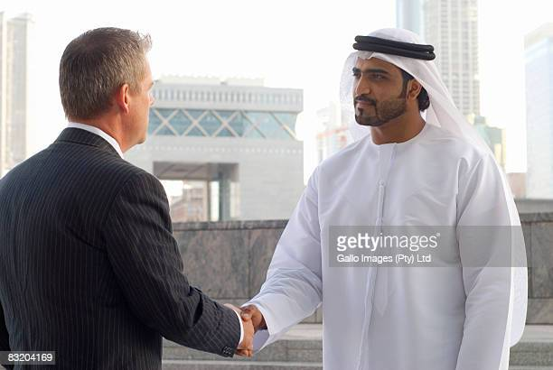 Man in traditionally Middle Eastern attire shaking hands with Western businessman, Dubai cityscape in background, UAE