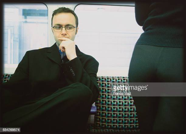 Man in Train Looking at Woman's Buttocks