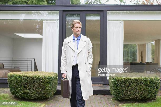 Man in Trench Coat Leaving Modern House