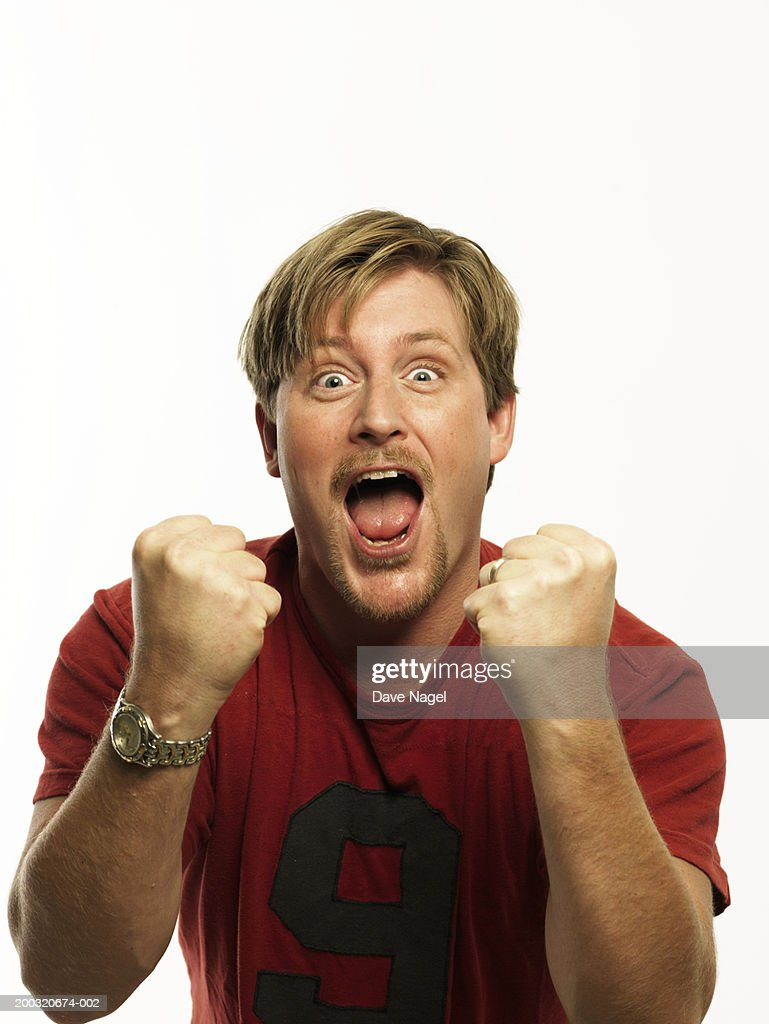 Man in t-shirt clenching fists, cheering, portrait, close-up : Stock Photo