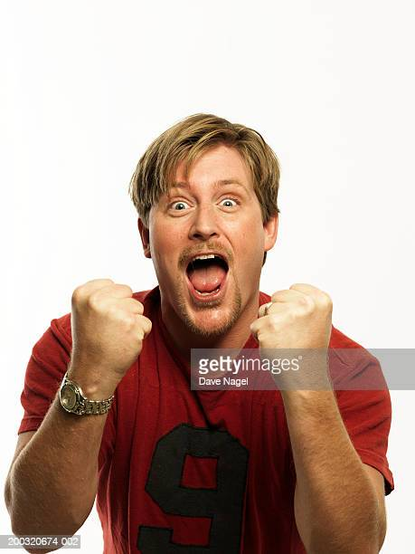 Man in t-shirt clenching fists, cheering, portrait, close-up