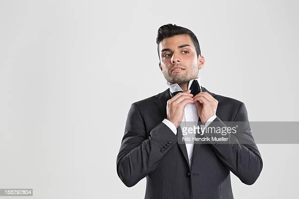 Man in tuxedo adjusting his bow tie