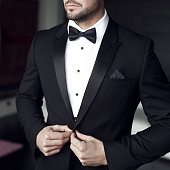 Man in tuxedo and bow tie posing