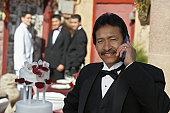 Man in tuxedo at Quinceanera, using mobile phone