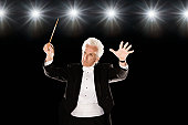 Man in tuxedo conducting under lights