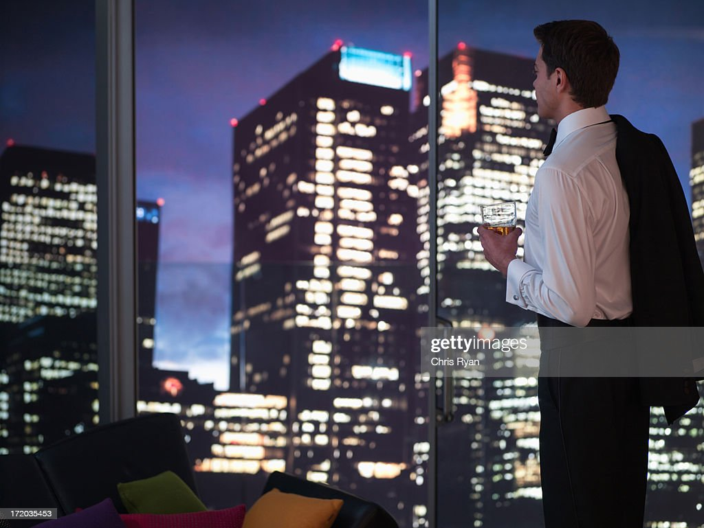 Man in tuxedo drinking cocktail with cityscape in background
