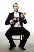 Man in tuxedo playing the ukulele