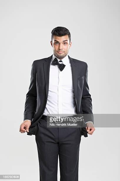 Man in tuxedo pulling at empty pockets
