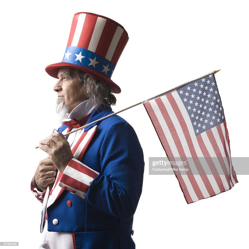 Man in Uncle Sam's costume holding american flag, studio shot
