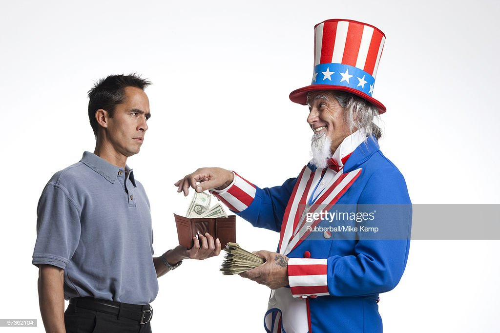 Man in Uncle Sam's costume taking money from other man, studio shot