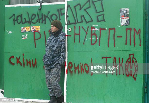 A man in uniform guards a gate covered with grafitti painted by supporters of Ukrainian opposition leader Viktor Yushchenko in central Kiev 02...