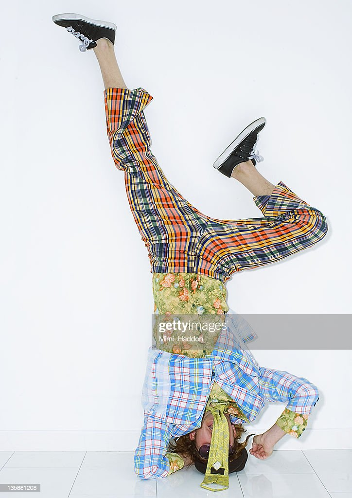 Man in Vintage Clothing Doing a Headstand