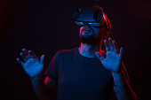 Shocked young man gesturing with hands and looking up while standing in black room under blue and red light