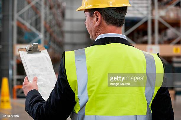 Man in warehouse holding clipboard, rear view