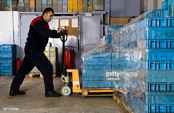 Man in warehouse pulling shipping crate.