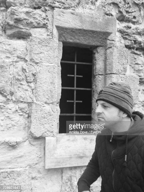 Man In Warm Clothing By Window