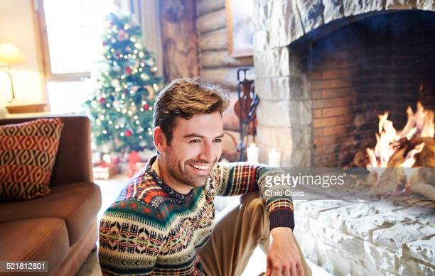Man in warm sweater enjoying fireplace
