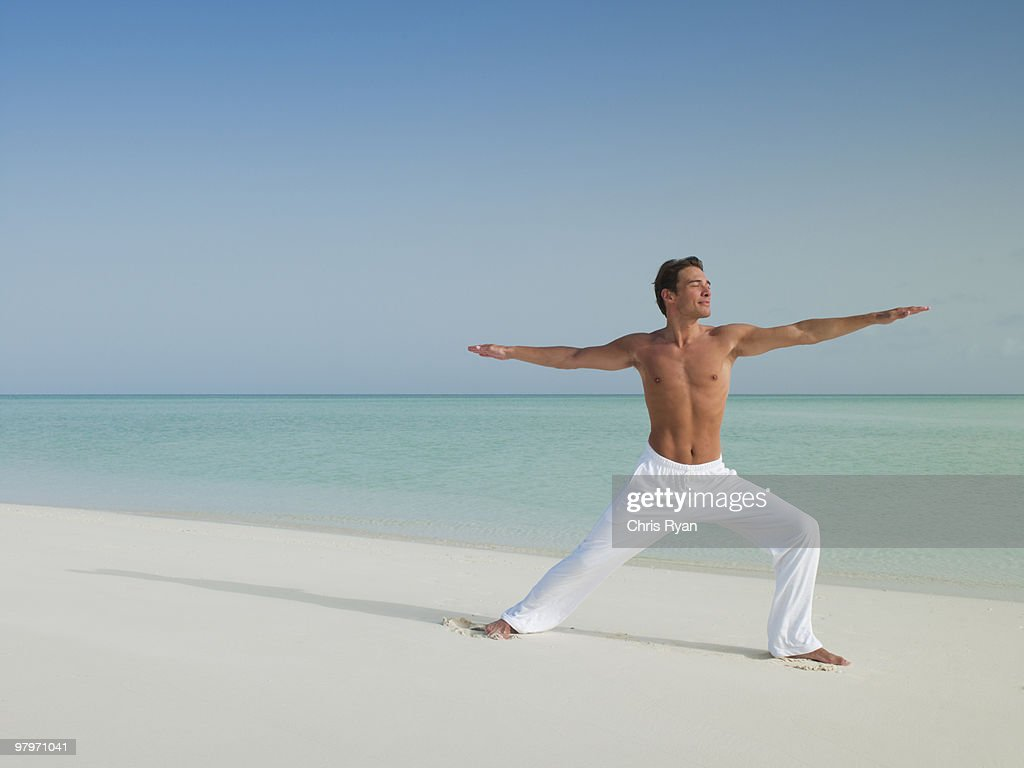 Man in warrior 2 yoga pose on beach : Stock Photo