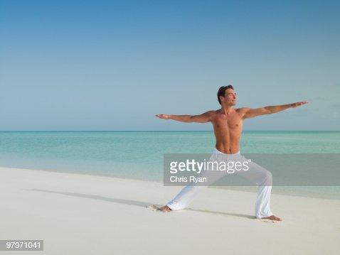 Man in warrior 2 yoga pose on beach : Stock Photo