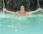 Man in water with outstretched arms, falling water splashing off hands