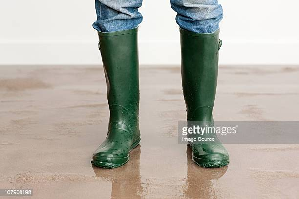 Man in wellington boots on flooded floor