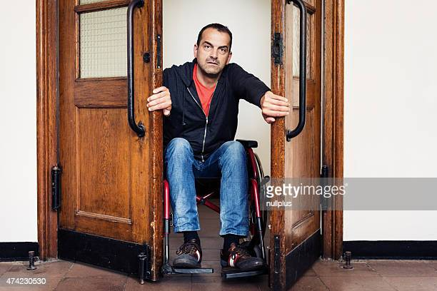 man in wheelchair having trouble going through door