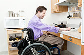 Man in wheelchair with spinal cord injury adjusting heat on an accessible stove