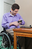 Man in wheelchair with spinal cord injury challenged with hand dexterity using his cell phone