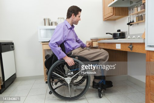 Man in wheelchair with spinal cord injury opening a drawer in an accessible kitchen : Stock Photo