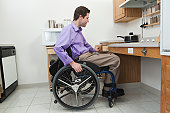 Man in wheelchair with spinal cord injury opening a drawer in an accessible kitchen