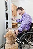 Man in wheelchair with spinal cord injury opening a refrigerator and petting his service dog