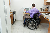Man in wheelchair with spinal cord injury opening accessible microwave